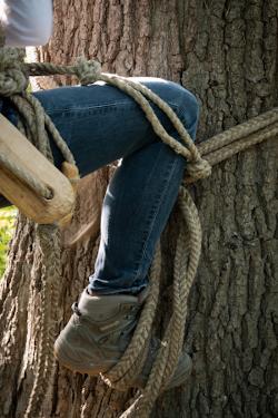 Angewinkeltes Bein an Baumstamm mit einfachem Kletterseil